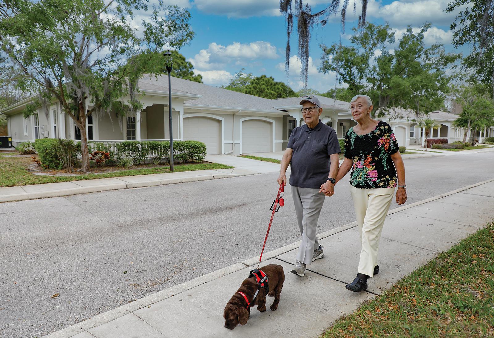 couple walking dog down street by villas
