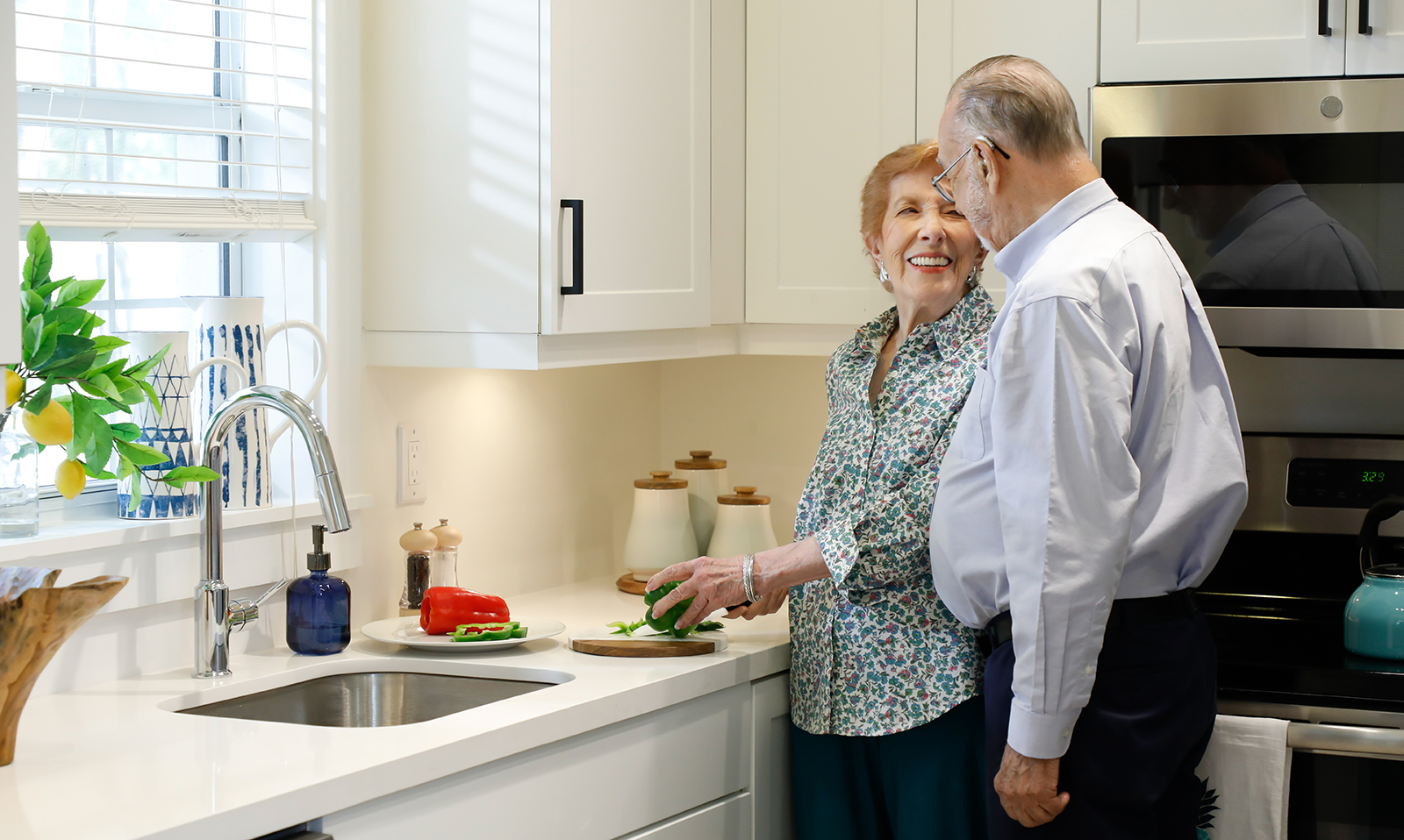 couple standing by sink in kitchen