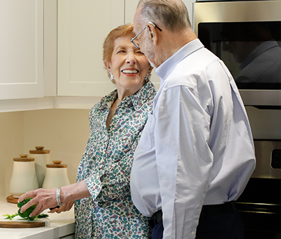 Couple standing at sink in kitchen